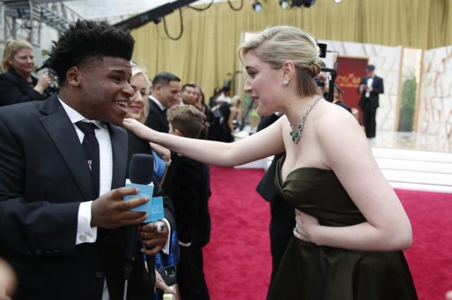 "In this Feb. 9, 2020 file photo, Greta Gerwig, right, talks to Jerry Harris on the red carpet at the Oscars at the Dolby Theatre in Los Angeles. Harris, the star of the Netflix documentary series ""Cheer,"" was arrested Thursday, Sept. 17 on child pornography charges. (AP Photo/John Locher File)"