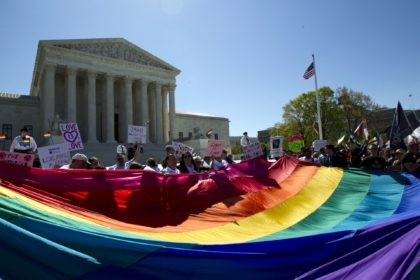 In this April 28, 2015 file photo, demonstrators stand in front of a rainbow flag of the Supreme Court in Washington. In 2019, there were slightly less than 1 million same-sex couple households in the U.S., and a majority of those couples were married. New figures released Thursday, Sept. 17, …