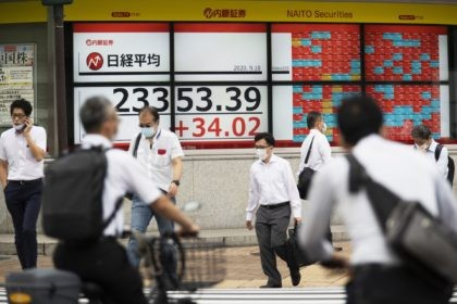 Men walk by screens showing Japan's Nikkei 225 index at a securities firm in Tokyo on Friday, Sept. 18, 2020. Asian shares were slightly higher Friday despite some investor attention shifting again to the uncertainties in global economies amid the coronavirus pandemic, as reflected in the overnight fall on Wall …