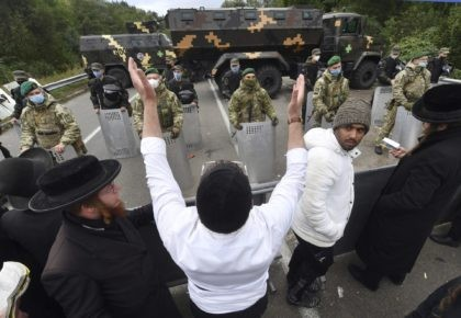 Hasidic Jewish pilgrims gather in front of Ukrainian border guards at the checkpoint Novaya Guta near Novaya Guta, Belarus, Friday, Sept. 18, 2020. Ukrainian officials say that thousands of Hasidic Jewish pilgrims stuck on the Ukrainian border due to coronavirus restrictions have started turning back. About 2,000 ultra-Orthodox Jewish pilgrims …
