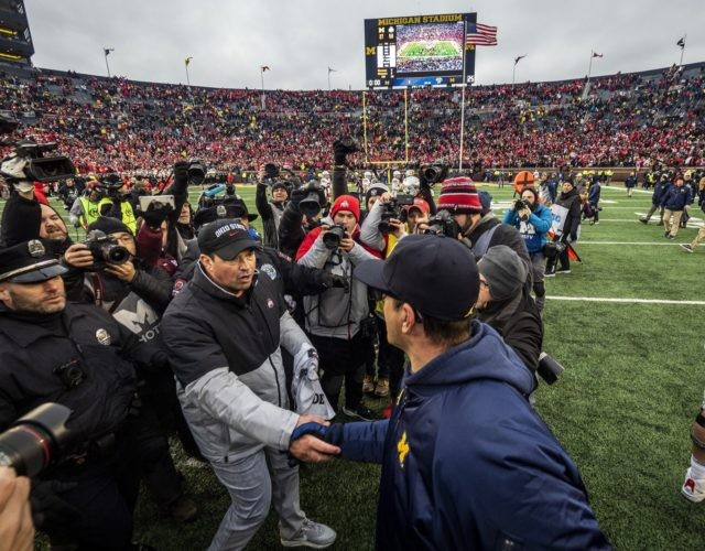 In this Nov. 30, 2019, file photo, Ohio State head coach Ryan Day, front left, shakes hands with Michigan head coach Jim Harbaugh, front right, after an NCAA college football game in Ann Arbor, Mich. The Big Ten's third football schedule of the 2020 season is highlighted by Michigan-Ohio State …