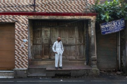 A man wearing a mask as protection against the coronavirus stands in front of a closed shop in Dharmsala, India, Wednesday, Sept. 23, 2020. The nation of 1.3 billion people is expected to become the pandemic's worst-hit country within weeks, surpassing the United States. (AP Photo/Ashwini Bhatia)