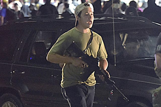 In this Tuesday, Aug. 25, 2020 file photo, Kyle Rittenhouse carries a weapon as he walks along Sheridan Road in Kenosha, Wis., during a night of unrest following the weekend police shooting of Jacob Blake. The way his lawyers tell it, the teenager wasn't a scared, gun enthusiast in over …