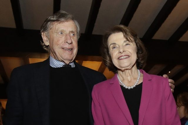 In this Nov. 6, 2018, file photo, U.S. Sen. Dianne Feinstein, right, smiles next to husband Richard Blum at an election night event in San Francisco. Sen. Feinstein's husband, University of California Regent Richard Blum, was named Thursday, Sept. 24, 2020, by the state auditor's office as one of the …
