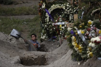 A cemetery worker digs a grave in a section of the Valle de Chalco Municipal Cemetery which opened early in the coronavirus pandemic to accommodate the surge in deaths, on the outskirts of Mexico City, Thursday, Sept. 24, 2020.(AP Photo/Rebecca Blackwell)