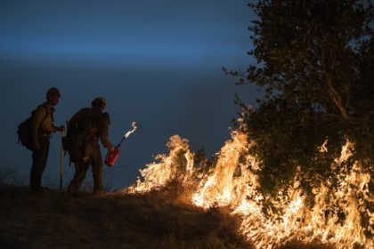 In this Sept. 11, 2020, file photo, firefighters light a controlled burn along Nacimiento-Fergusson Road to help contain the Dolan Fire near Big Sur, Calif. Rain showers fell Thursday, Sept. 24, 2020, on the northwestern edges of fire-ravaged California but forecasters warned residents to not be fooled: a new round …