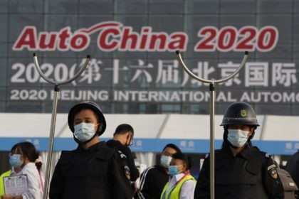 Security guards wearing masks and armed with restrainers stand guard at the entrance to the Auto China 2020 show in Beijing, China on Saturday, Sept. 26, 2020. The auto show, the first major in-person sales event for any industry since the coronavirus pandemic began, opens Saturday in a sign the …