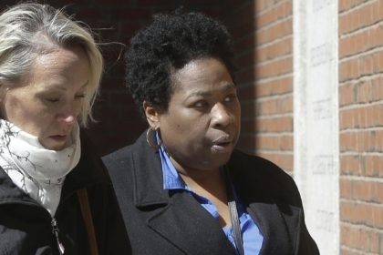 In this March 25, 2019, file photo, Niki Williams, right, a college entrance exam administrator, arrives at federal court in Boston to face charges in a nationwide college admissions bribery scandal. Williams is scheduled to plead guilty to charges on Friday, Sept. 25, 2020. (AP Photo/Steven Senne, File)