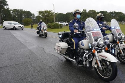 A Louisiana State Police motorcycle honor guard precedes the hearse carrying the body of Master Trooper Chris Hollingsworth, Friday, Sept. 25, 2020, in West Monroe, La. Hollingsworth, killed in a car crash hours after he was told he would be fired for his role in the death of a Black …
