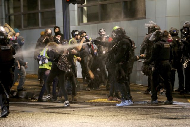 Protesters demanding the end of police violence against Black people are sprayed by police during a demonstration in Portland, Ore., on Wednesday, Sept. 23, 2020. Protesters in Portland hurled Molotov cocktails at officers in Oregon's largest city during a demonstration over a Kentucky grand jury's decision to not indict officers …