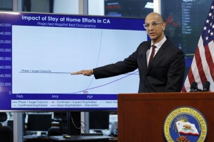 In this April 1, 2020, file photo, Dr. Mark Ghaly, secretary of the California Health and Human Services, gestures to a chart showing the impact of the mandatory stay-at-home orders, during a news conference in Rancho Cordova, Calif. Dr. Ghaly urged state residents to renew their efforts to prevent spread …