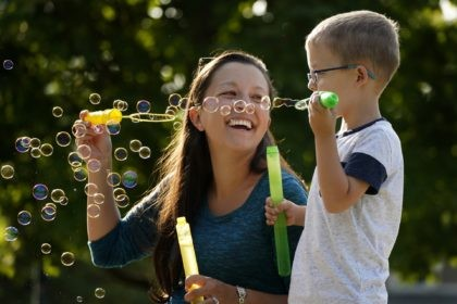 Claire Reagan plays with her son Evan, 5, Monday, Sept. 21, 2020, outside her home in Olathe, Kan. Reagan is keeping her son from starting kindergarten and her daughter Abbie, 3, from preschool due to concerns about the coronavirus pandemic. (AP Photo/Charlie Riedel)