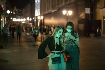 Two women wearing face masks to protect against coronavirus look at a smartphone in the center of Moscow, Russia, Friday, Sept. 25, 2020. Moscow authorities have issued a recommendation for the elderly to stay at home and for employers to allow as many people as possible to work remotely, following …
