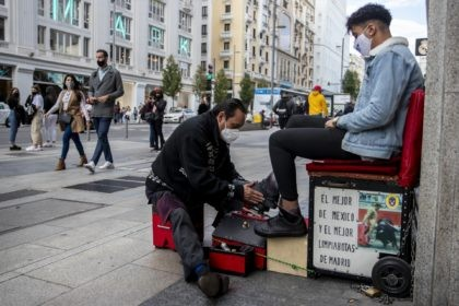 A shoe shiner wearing a face mask to prevent the spread of coronavirus cleans a shoes of a customer at Gran Via avenue in downtown Madrid, Spain, Saturday, Sept. 26, 2020. Spain's health minister has reiterated his plea for Madrid's regional authorities to apply more stringent restrictions on mobility in …