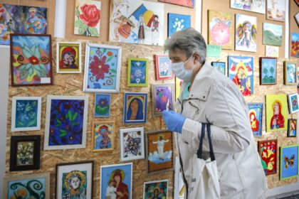 A woman wearing a face mask for protection against COVID-19 infection, passes by religious themed works by children on her way to cast her vote in local elections at a school in Bucharest, Romania, Sunday, Sept. 27, 2020. Polls have opened in Romania's municipal election, which is being seen as …