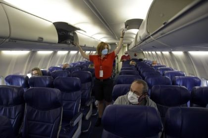 In this May 24, 2020, file photo, a Southwest Airlines flight attendant prepares a plane bound for Orlando, Fla. for takeoff at Kansas City International airport in Kansas City, Mo. About 40,000 workers in the airline industry are facing layoffs on Thursday, Oct. 1, unless Congress comes up with another …