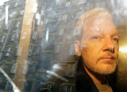In this Wednesday May 1, 2019 file photo buildings are reflected in the window as WikiLeaks founder Julian Assange is taken from court, where he appeared on charges of jumping British bail seven years ago, in London. A lawyer for Julian Assange said Friday, Sept. 25, 2020 that the WikiLeaks …