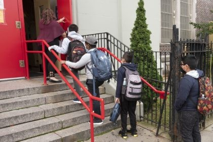 A teacher leads her students into an elementary school in the Brooklyn borough of New York on Tuesday, Sept. 29, 2020, as hundreds of thousands of elementary school students are heading back to classrooms in the city, resuming in-person learning during the coronavirus pandemic. The coronavirus is infecting a rising …