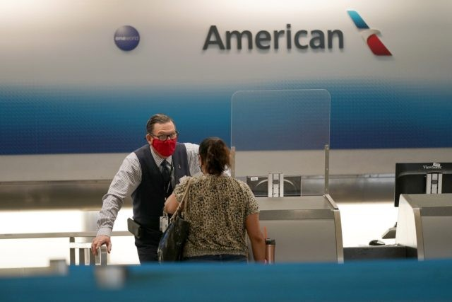 American Airlines ticket agent Henry Gemdron, left, works with a customer at Miami International Airport during the coronavirus pandemic, Wednesday, Sept. 30, 2020, in Miami. The airline industry has been decimated by the pandemic. The Payroll Support Program given to the airlines as part of the CARES Act runs out …