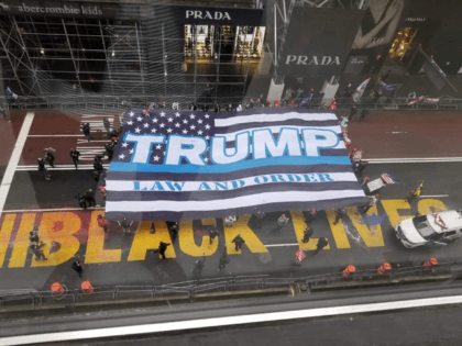 "The 75-foot by 50-foot flag, which reads ""Trump: Law and Order,"" was unveiled over a painted ""Black Lives Matter"" mural on the street."