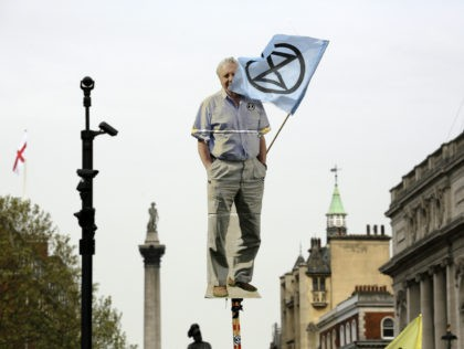 A cardboard cutout of David Attenborough is held up as protesters march toward parliament with Nelson's Column in the background, in London, Tuesday April 23, 2019, during a climate protest. The non-violent protest group, Extinction Rebellion, is seeking negotiations with the government on its demand to make slowing climate change …