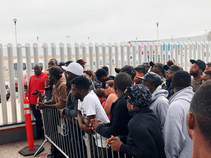 In this Sunday, July 28, 2019, photo, migrants in Tijuana, many from Cameroon, listen to names being called for those who can claim asylum that day in the US. English-speaking Cameroonians fleeing atrocities of their French-speaking government helped push Tijuana's asylum wait list to 10,000 on Sunday, up from 4,800 …
