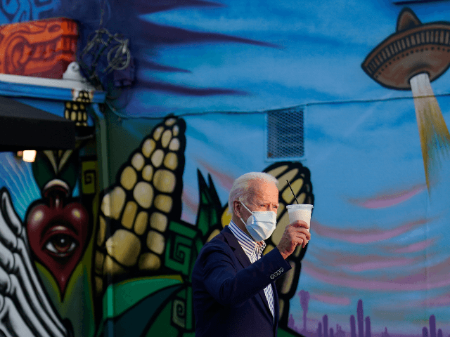 Democratic presidential candidate former Vice President Joe Biden holds a beverage as he leaves Barrio Cafe in Phoenix, Thursday, Oct. 8, 2020, during their small business bus tour. (AP Photo/Carolyn Kaster)