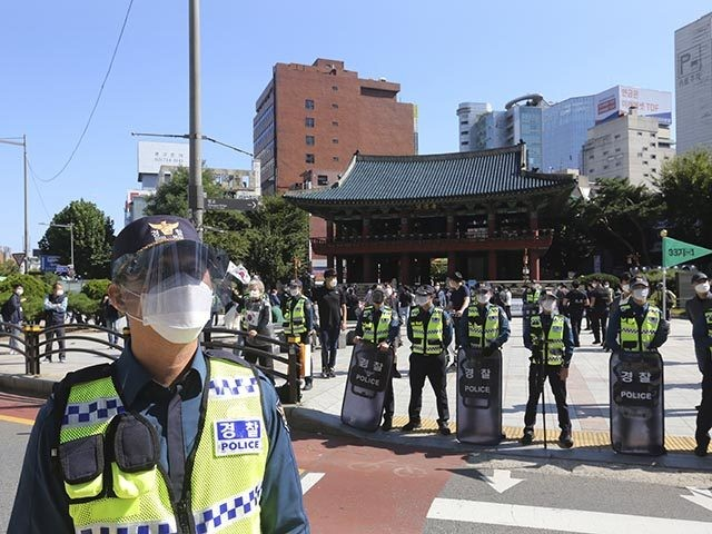 South Korean police officers wearing face masks and face shields stand guard to block protesters' possible rallies against the government in Seoul, South Korea, Friday, Oct. 9, 2020. Seoul city temporarily banned outdoor rallies with 10 or more people over infection risks against the spread of the coronavirus. (AP Photo/Ahn …
