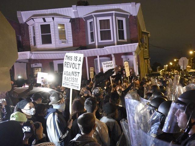 La policía vigila a manifestantes en Filadelfia el 27 de octubre del 2020, luego de que la muerte de un individuo de raza negra a manos de la policía generase protestas. (AP Photo/Michael Pérez)