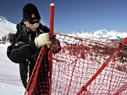Race crew course worker Guy Bien of Mammoth Lakes, Calif., fixes a safety fence on the downhill course at Mammoth Ski Resort for the U.S. Alpine National Ski Championships Wednesday, March 30, 2005, for the first day of the downhill training run after Tuesdays cancellation due to high winds and …
