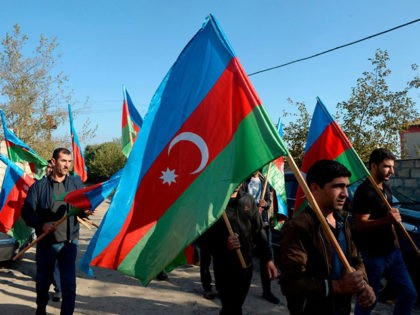 TOPSHOT - Men walk with Azerbaijani flags during a funeral ceremony of an Azeri serviceman who is said was killed in fighting with Armenian separatists over the breakaway Nagorny Karabakh region, in a settlement in Azerbaijan's Beylagan district on September 30, 2020. (Photo by TOFIK BABAYEV / AFP) (Photo by …