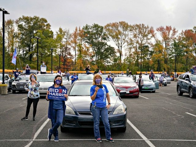 BRISTOL, PA - OCTOBER 24: Standing near their cars, supporters listen as Democratic presidential nominee Joe Biden speaks during a drive-in campaign rally at Bucks County Community College on October 24, 2020 in Bristol, Pennsylvania. Biden is making two campaign stops in the battleground state of Pennsylvania on Saturday. (Photo …