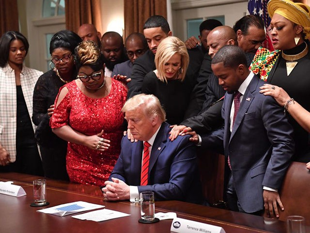 TOPSHOT - US President Donald Trump (C) stands in a prayer circle with African-American leaders in the Cabinet Room of the White House in Washington, DC, on February 27, 2020. (Photo by Nicholas Kamm / AFP) (Photo by NICHOLAS KAMM/AFP via Getty Images)