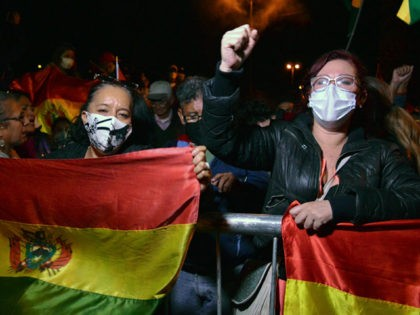 People hold a protest against the results in the country's presidential election after Luis Arce of the Movement for Socialism (MAS) party claimed victory in Sunday's election, in front of the office where departmental votes are counted, in Cochabmba on October 20, 2020. (Photo by FERNANDO CARTAGENA / AFP) (Photo …
