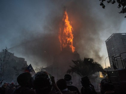 SANTIAGO, CHILE - OCTOBER 18: Firemen attempt to put out a church which has caught fire during a protest on October 18, 2020 in Santiago, Chile. A series of protests and social unrest arose on October 18, 2019, after a subway fare increase. It developed in a movement demanding improvements …