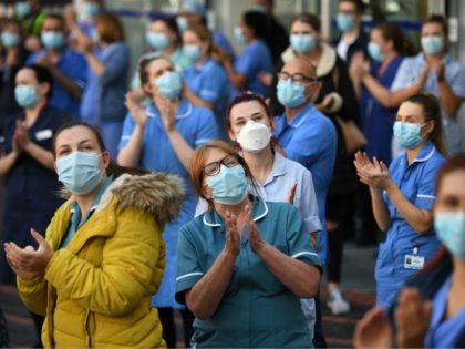 Members of staff of the Leeds General Infirmary participate in a national NHS (National Health Service) celebration clap outside the hospital in Leeds on July 5, 2020, to mark its 72nd anniversary. - This year's celebration is particularly poignant given the challenging conditions NHS staff have had to work under …