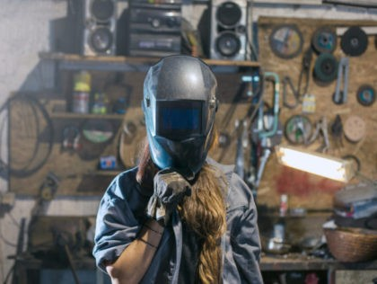 woman with welding mask in workshop