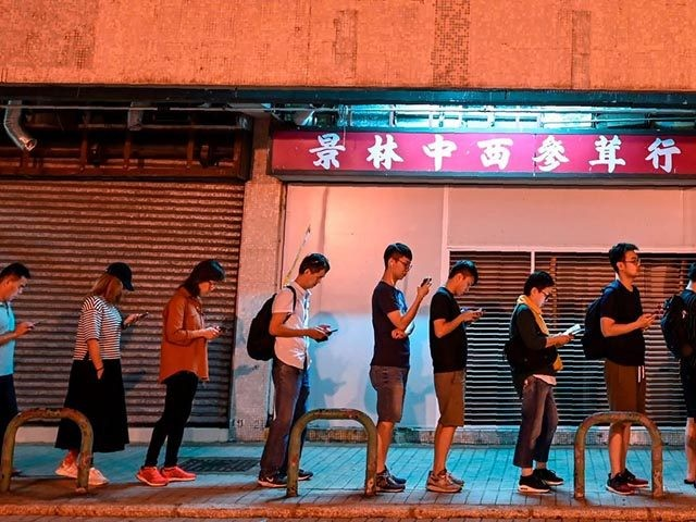 People queue to cast their vote during the district council elections in Tseung Kwan O district in Hong Kong on November 24, 2019. - Hong Kong's voters turned out in record numbers on November 24 for local council elections that the city's pro-democracy movement hopes will pile pressure on the …
