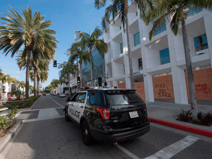 Police patrol past boarded up stores on the iconic Rodeo Drive, after demonstrators protested the death of George Floyd in Beverly Hills, California on May 31, 2020. - Thousands of National Guard troops patrolled major US cities after five consecutive nights of protests over racism and police brutality that boiled …