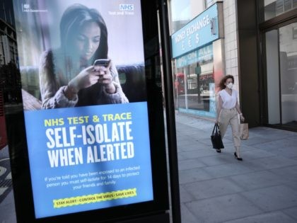 LONDON, ENGLAND - JUNE 15: A woman walks past an NHS Test and Trace advertisement on Oxford Street as stores reopen following closure due to the coronavirus outbreak on June 15, 2020 in London, United Kingdom. The British government have relaxed coronavirus lockdown laws significantly from Monday June 15, allowing …