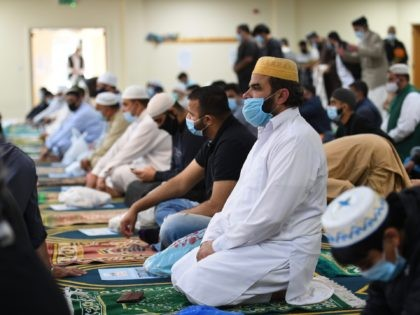 Worshippers sit on their personal prayer mats, socially distanced and wearing facemasks during Friday prayers at Madina Masjid, Sheffield's central mosque, in Sheffield, northern England, on July 24, 2020. - The Sheffield central mosque has taken a number of safety measures including temperature checks, taking details for contact tracing purposes, …