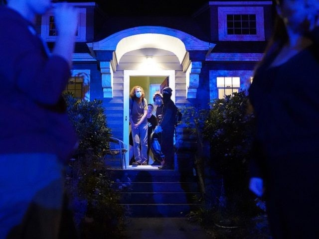 PORTLAND, OR - AUGUST 10: Protesters take shelter in the front door of a house near the Portland Police Bureau North Precinct as the homeowners tell passing crowds to take shelter inside during a crowd dispersal on August 10, 2020 in Portland, Oregon. Neighborhood residents regularly aid protesters as police …