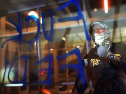 PORTLAND, OR - AUGUST 21: A federal officers reads the words Fuck Feds written in graffiti on the front of the Immigration and Customs Enforcement (ICE) detention facility early in the morning on August 21, 2020 in Portland, Oregon. For the second night in a row federal police clashed with …