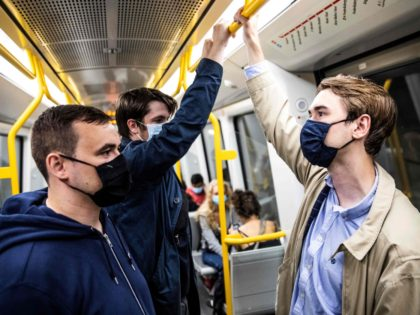 People wear mask on a metro train in Copenhagen shortly after midnight, on August 22, 2020, as the Danish government imposed to wear face mask or visor in public transport to prevent the spread of the new coronavirus. (Photo by Olafur STEINAR GESTSSON / Ritzau Scanpix / AFP) / Denmark …