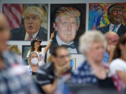 TOPSHOT - A woman waves an American flag as President Trump supporters watch the presidential debate at the Trump Victory Campaign center in Katy, Texas on September 29, 2020. - Joe Biden and Donald Trump exchanged heated barbs attacking each other's competence and credibility, in a fiery first presidential debate …