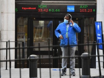 A stock trader checks his headphones outside the New York Stock Exchange (NYSE) in lower Manhattan on October 5, 2020 in New York City. - Stock markets bounced back on reports suggesting Donald Trump's health had improved after his positive test for the coronavirus, with traders also cheered by signs …