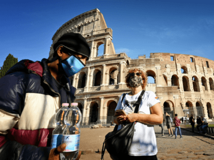 A street vendor and a woman both wearing face masks pass in front of The Colosseum in Rome on October 9, 2020. - Italy's government has made it mandatory to wear face protection outdoors, in an attempt to counter the spread of the coronavirus Covid-19 pandemic. (Photo by Alberto PIZZOLI …