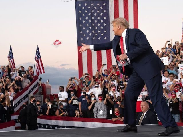 US President Donald Trump throws masks to supporters as he arrives to hold a Make America Great Again rally as he campaigns at Orlando Sanford International Airport in Sanford, Florida, October 12, 2020. (Photo by SAUL LOEB / AFP) (Photo by SAUL LOEB/AFP via Getty Images)