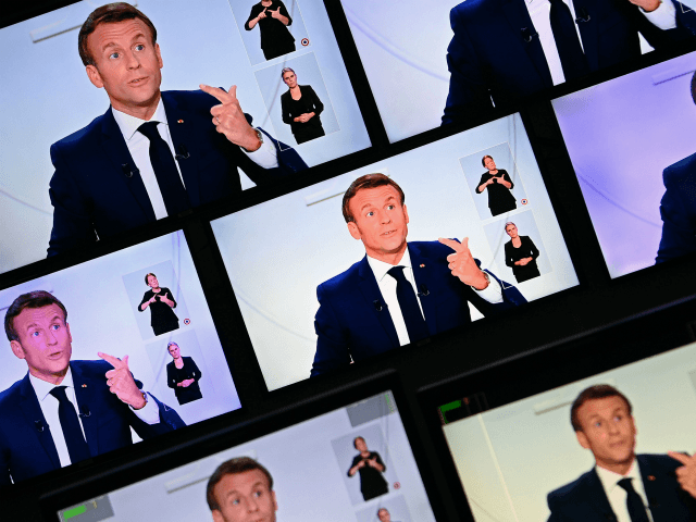 This picture shows screens displaying French President Emmanuel Macron as he addresses the nation during a televised interview from the Elysee Palace concerning the situation of the novel coronavirus Covid-19 in France, in Paris on October 14, 2020. - President Emmanuel Macron on Wednesday ordered a nighttime curfew for Paris …