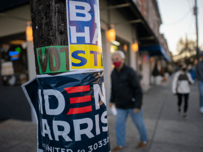 PHILADELPHIA, PA - OCTOBER 17: A man walks past a telephone pole affixed with several Biden Harris campaign posters on October 17, 2020 in Philadelphia, Pennsylvania. With the election only a little more than two weeks away, a new form of in-person early voting by using mail ballots, has enabled …